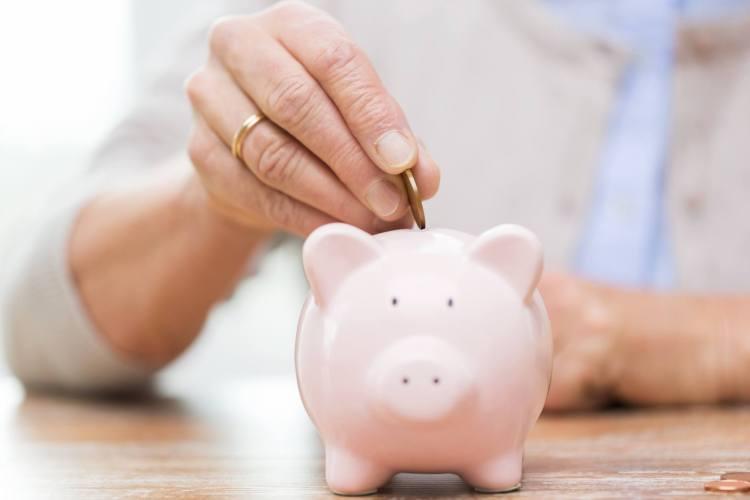 senior-woman-hand-putting-money-to-piggy-bank.jpg
